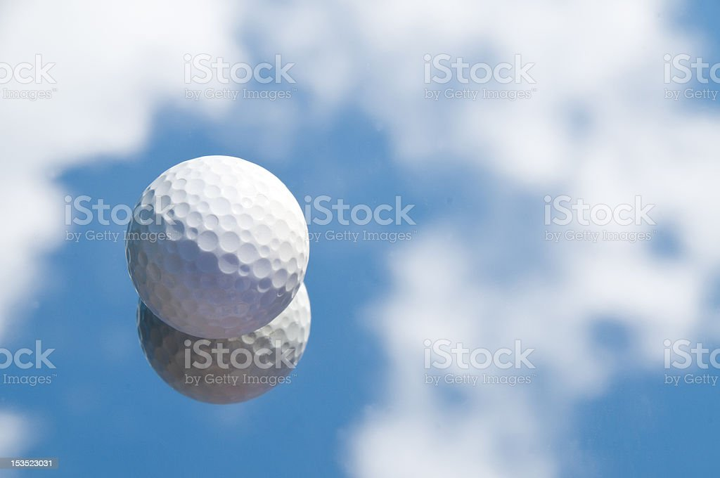 Golfball on mirror with reflected sky and clouds royalty-free stock photo