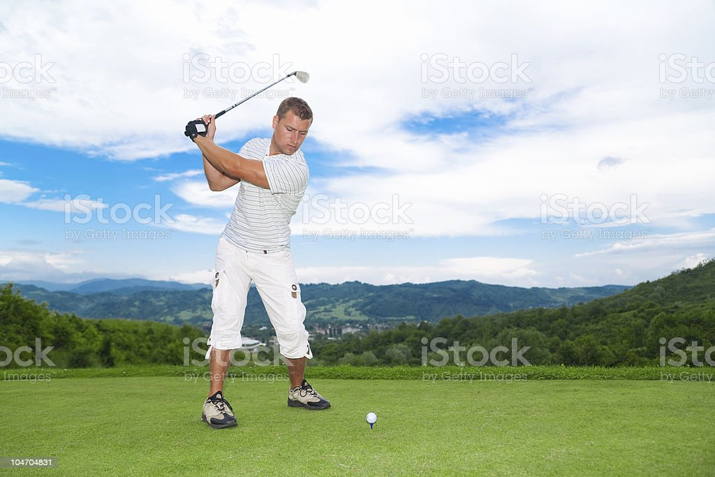 Golfer about to strike ball stock photo