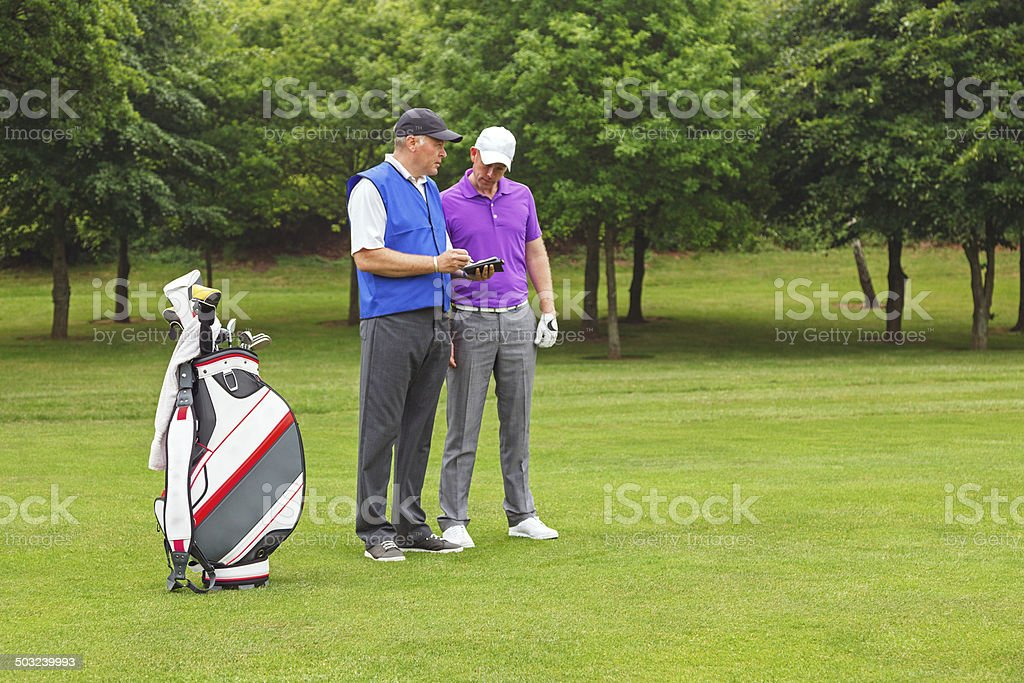 Golfer and caddy looking at a course guide stock photo