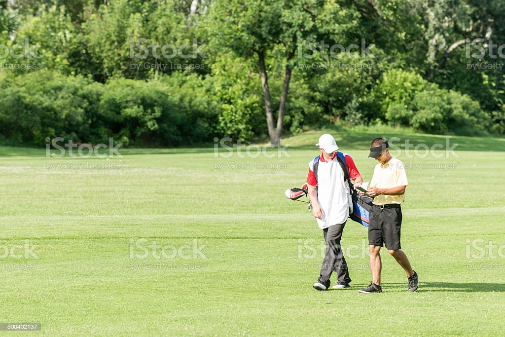 Golfer and caddy on a golf course stock photo
