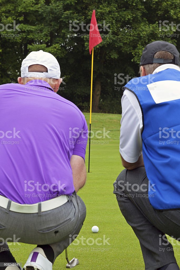 Golfer and caddy putting green. stock photo