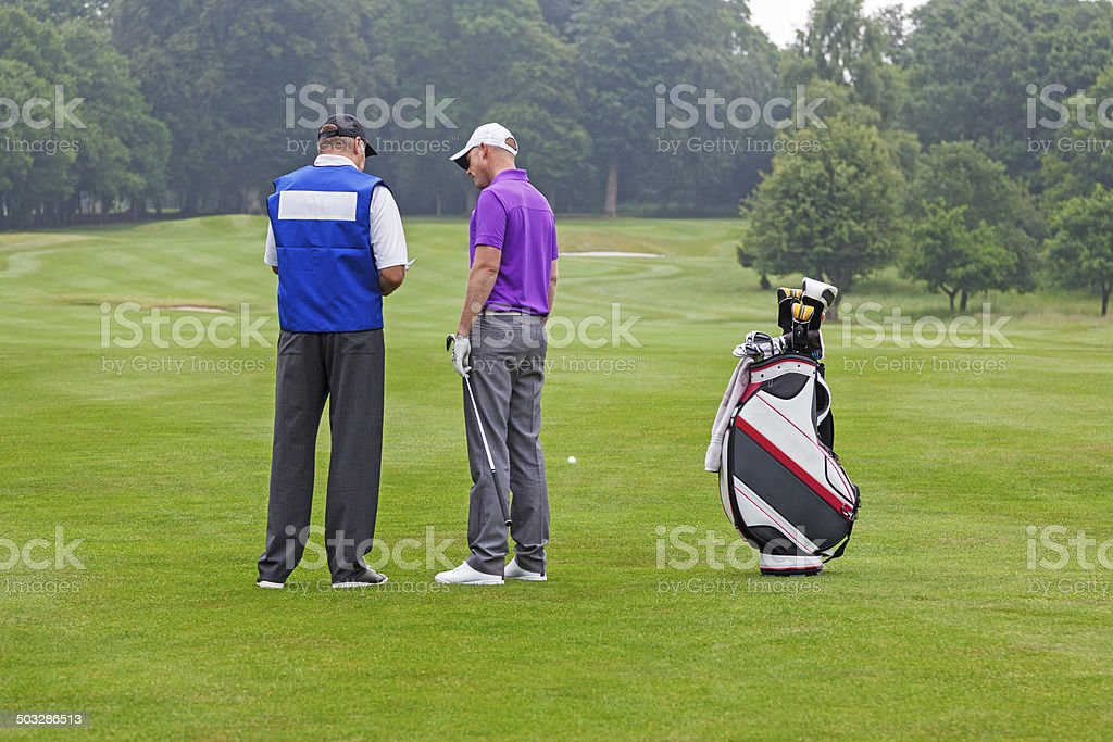 Golfer and caddy reading a course guide stock photo