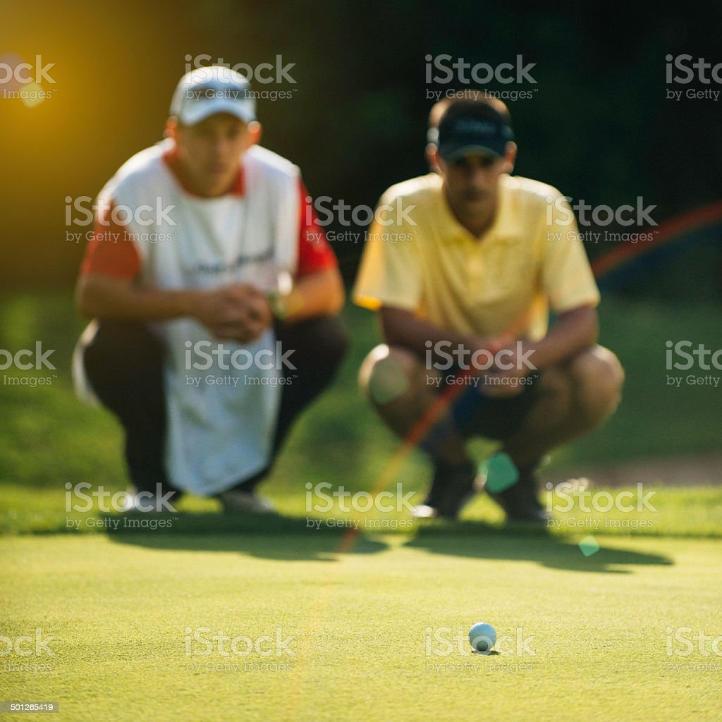 Golfer and caddy reading green stock photo