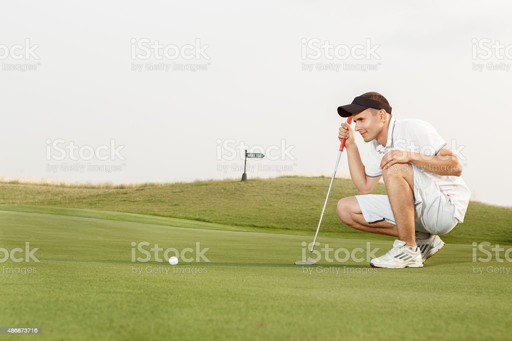 Golfer assessing his options to putt the ball stock photo