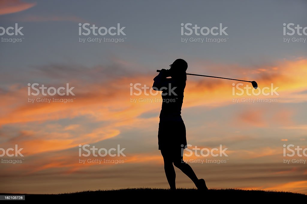 Golfer at sunset. stock photo