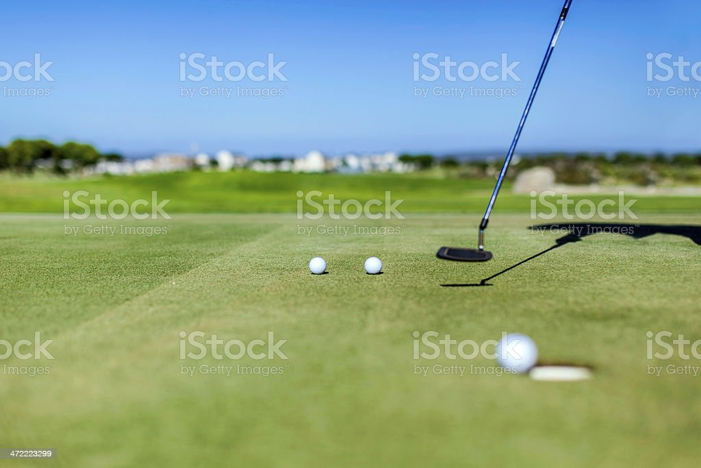Golfer busy practicing his putting skills on the golf course royalty-free stock photo