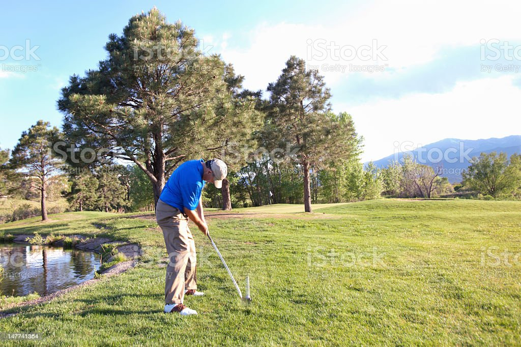 Golfer chipping from rough, showing club and ball motion stock photo
