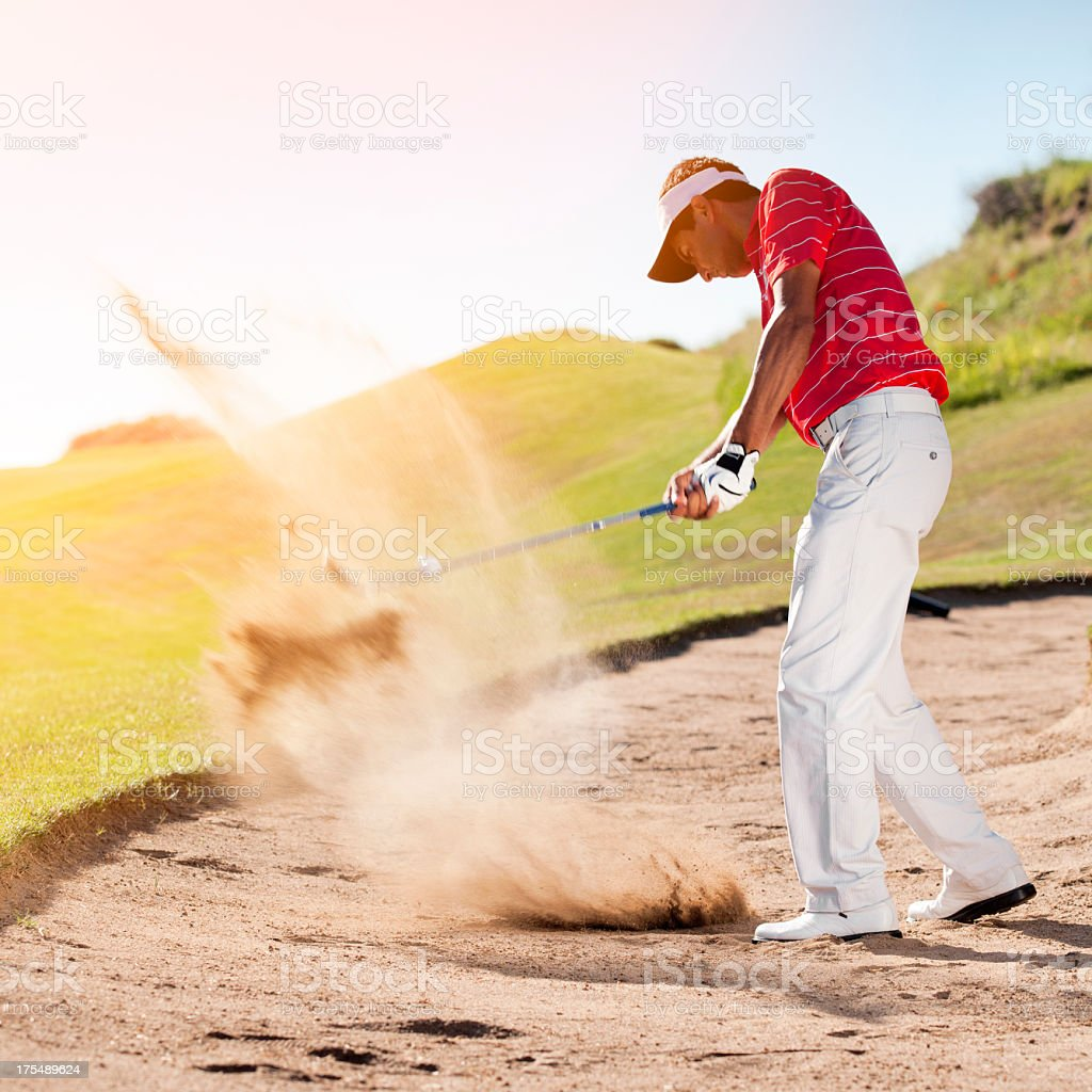 Golfer chipping the ball from sand trap stock photo