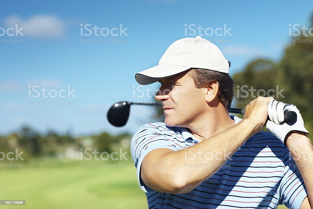 Golfer during the follow through of his swing stock photo