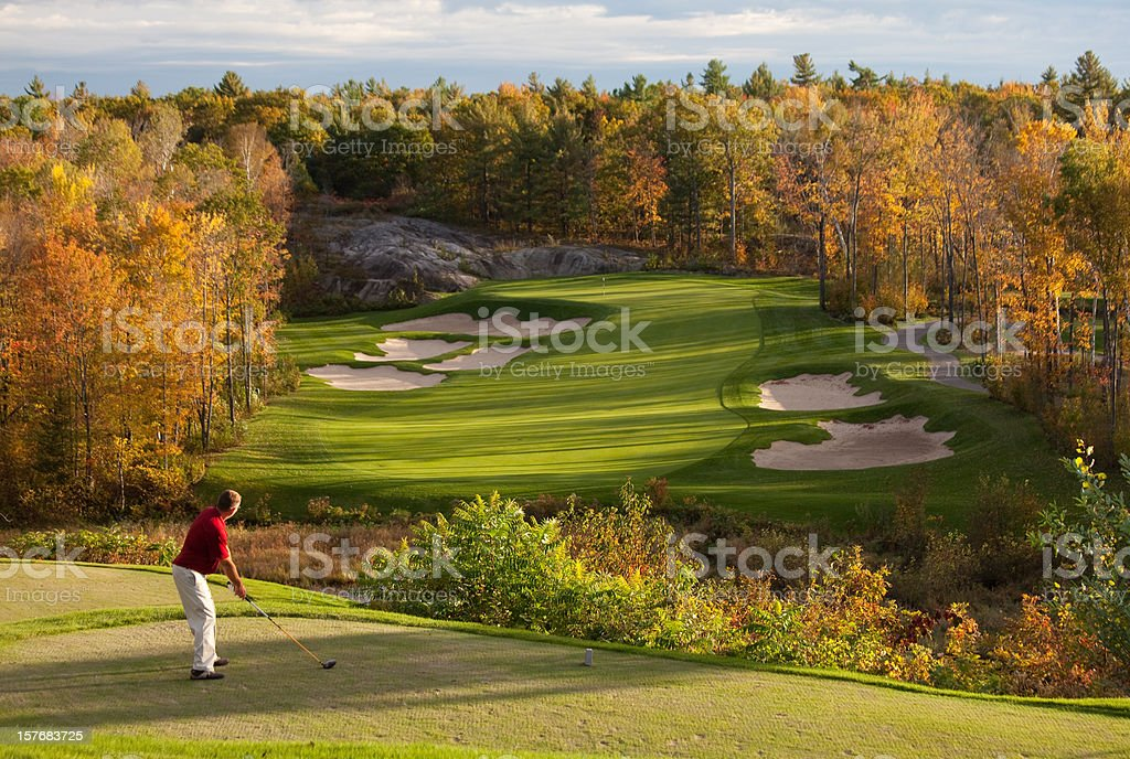 Golfer getting ready to swing on a beautiful fall day stock photo