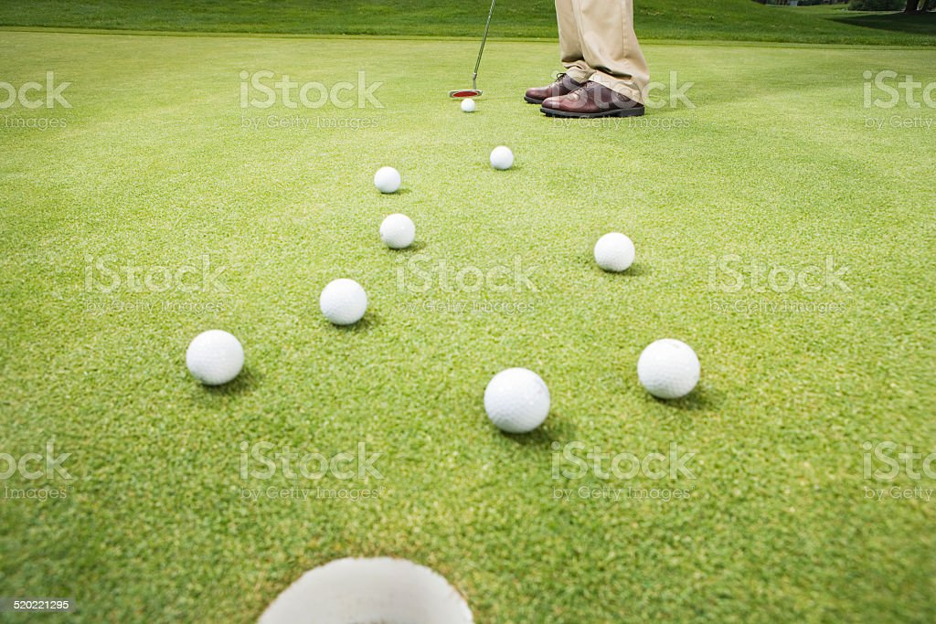 Golfer hitting ball through group of golf balls, low section stock photo