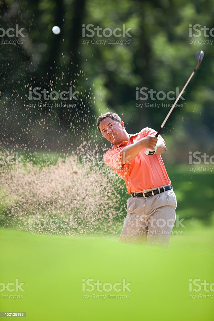 Golfer Hitting Golf Ball In Sand Hazard stock photo