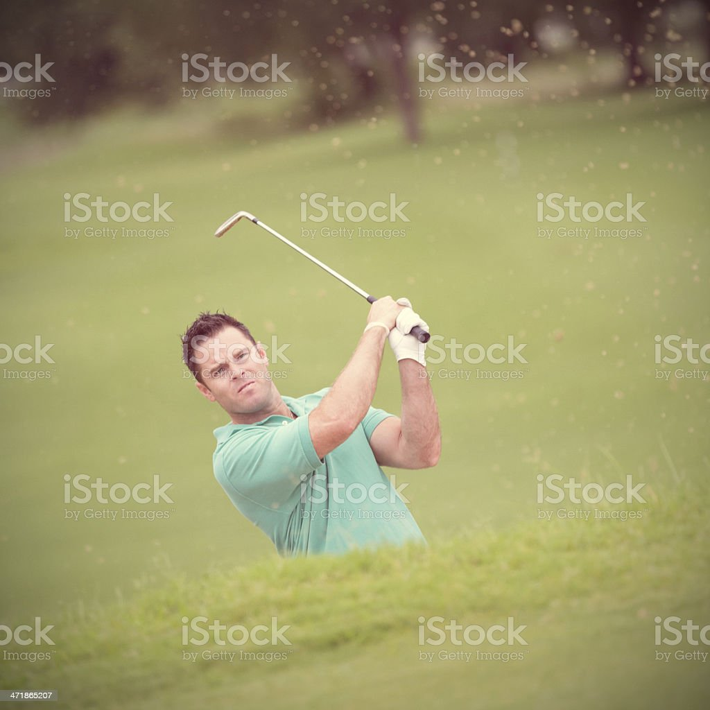 Golfer hitting golf ball out of sand trap on course stock photo
