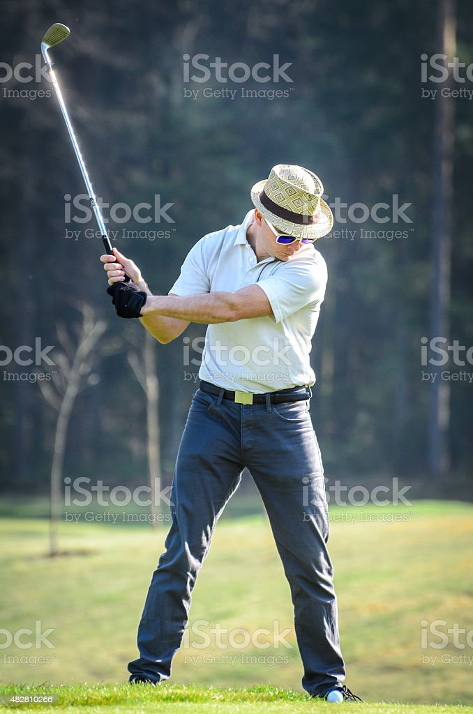 Golfer hitting golf shot with club on course stock photo