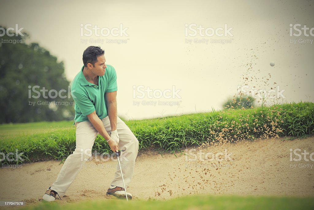 Golfer hitting his golf ball out of sand trap stock photo