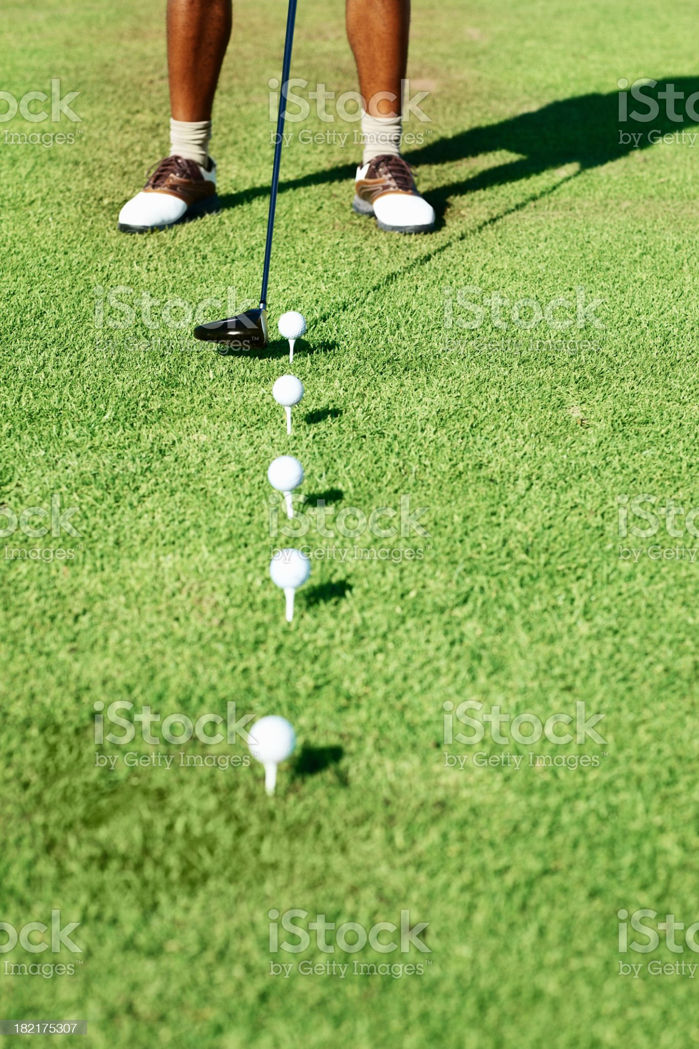 A golfer holding his club ready to hit the golf ball royalty-free stock photo
