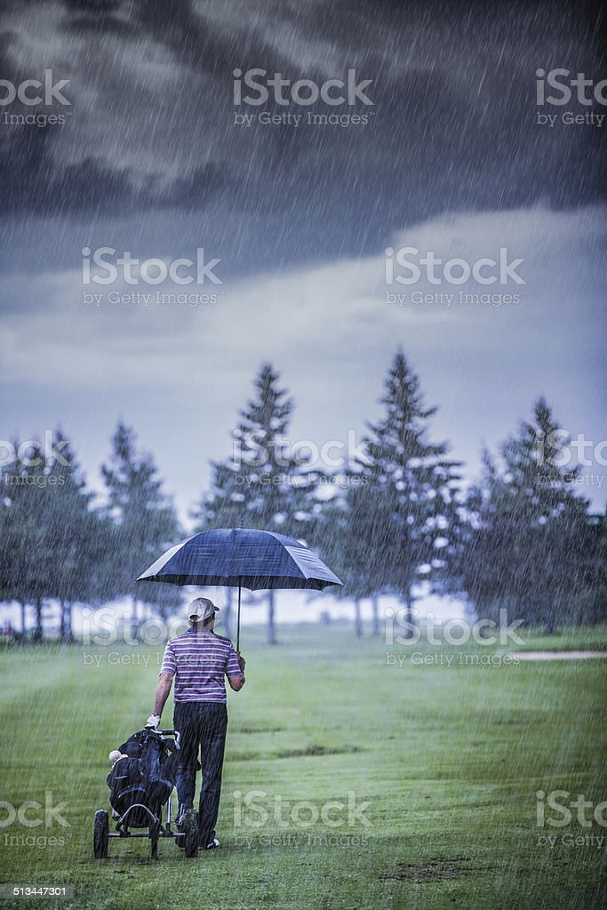 Golfer on a Rainy Day Leaving the Golf Course stock photo