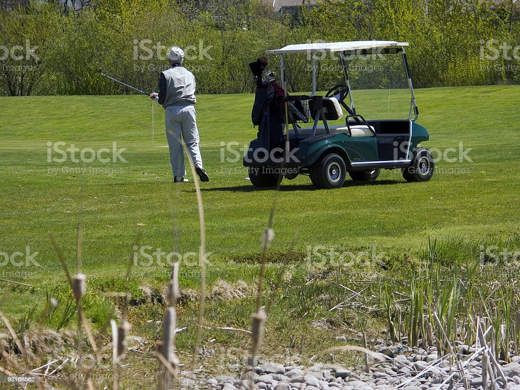 Golfer on Course with Golf Cart royalty-free stock photo