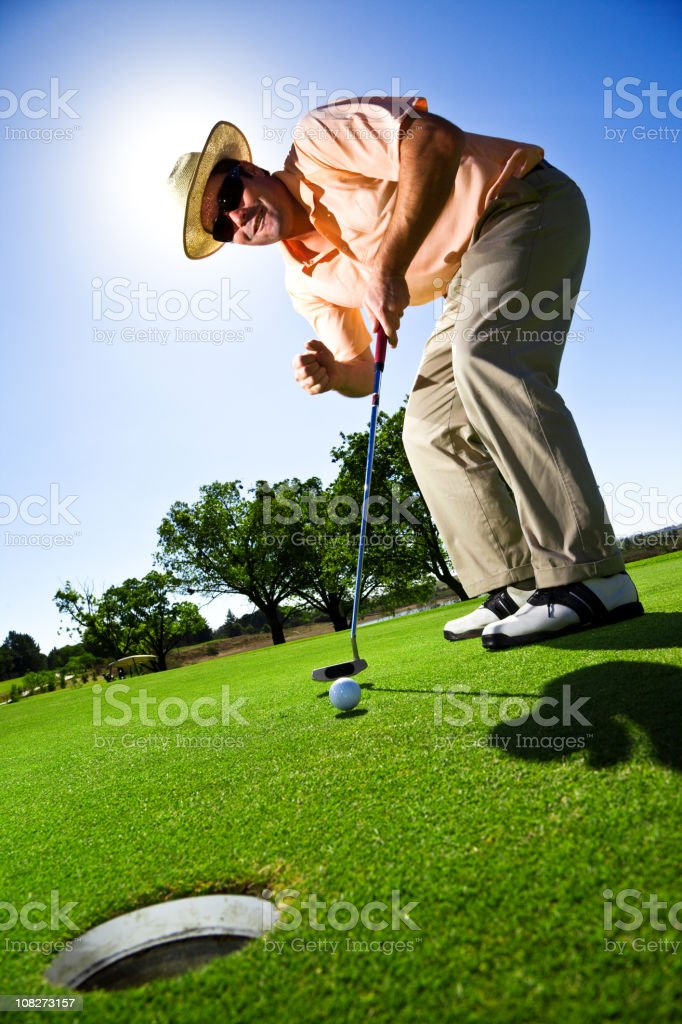 Golfer on the green putting stock photo