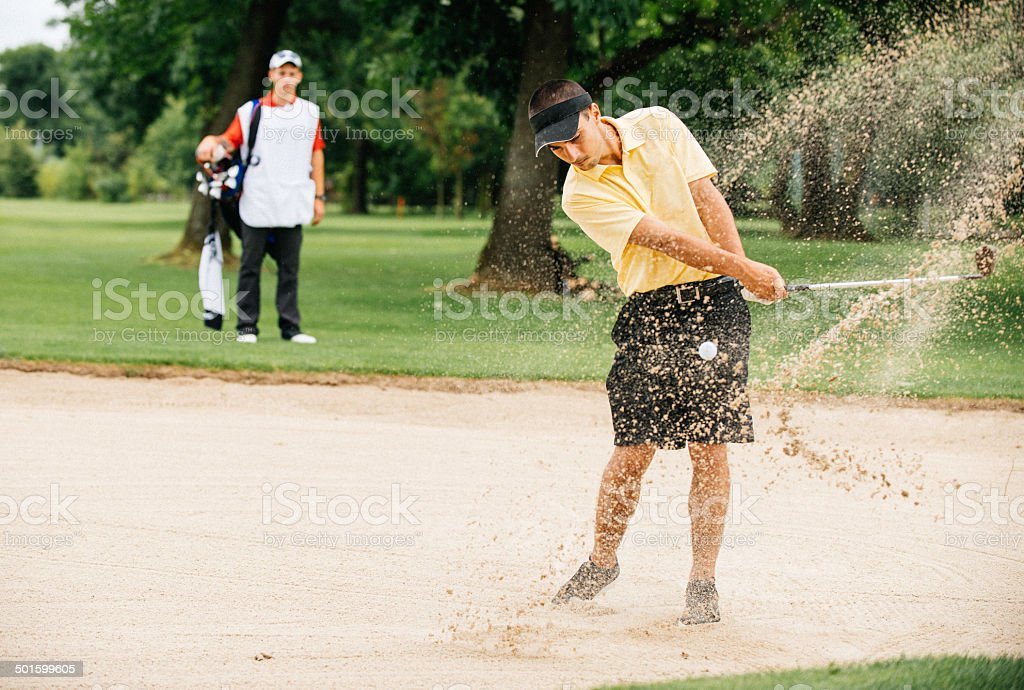 Golfer playing from sand trap stock photo