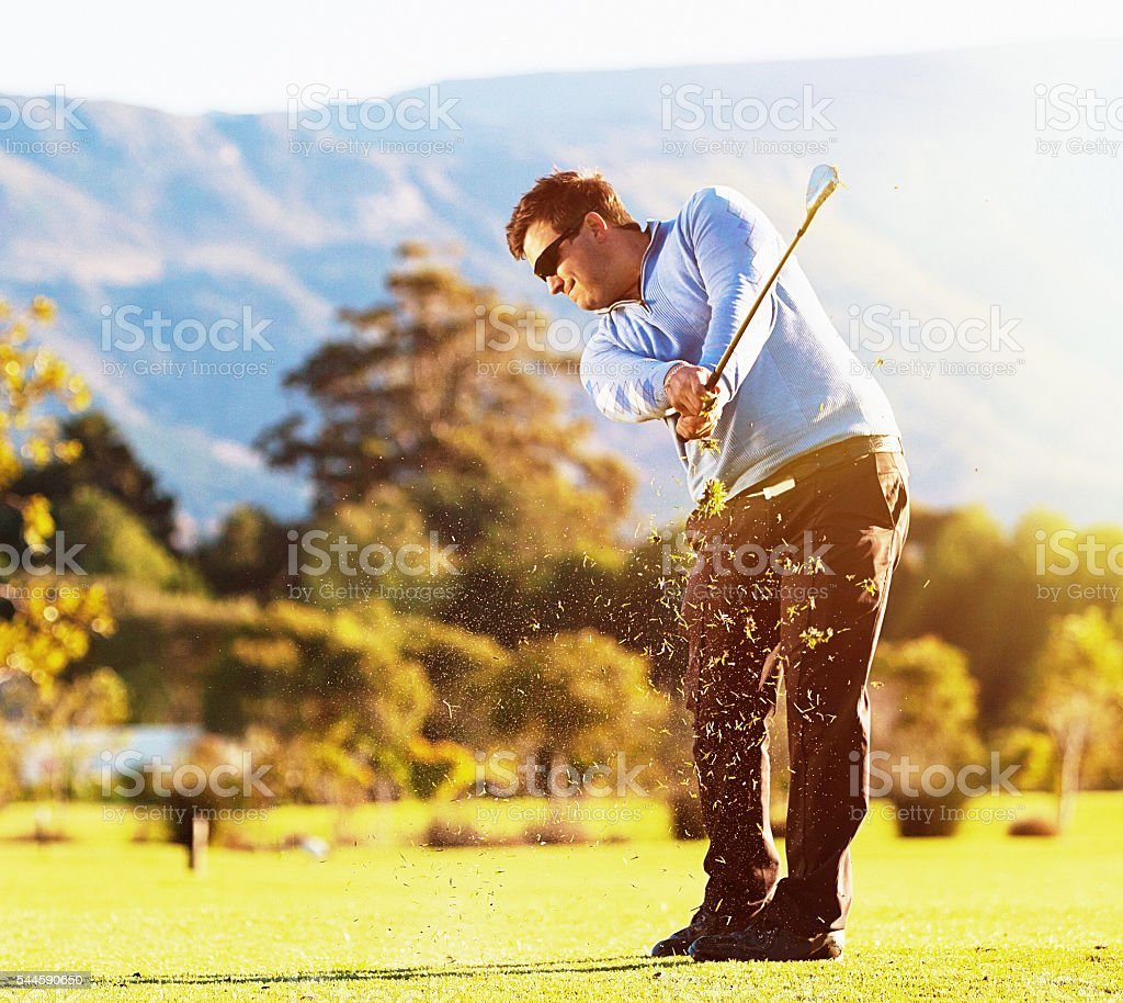 Golfer playing on idyllic sunlit golf course stock photo