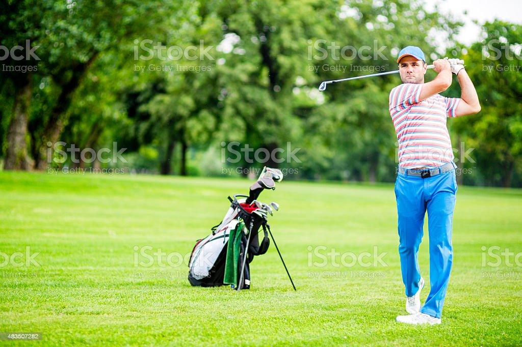 Golfer practicing and concentrating before and after shot stock photo