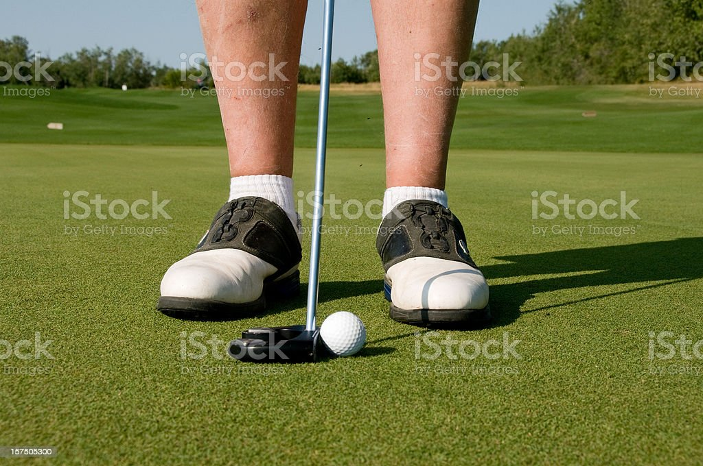 Golfer prepares to putt ball on greens stock photo