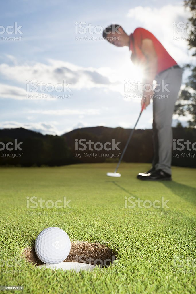 Golfer putting ball into cup. stock photo