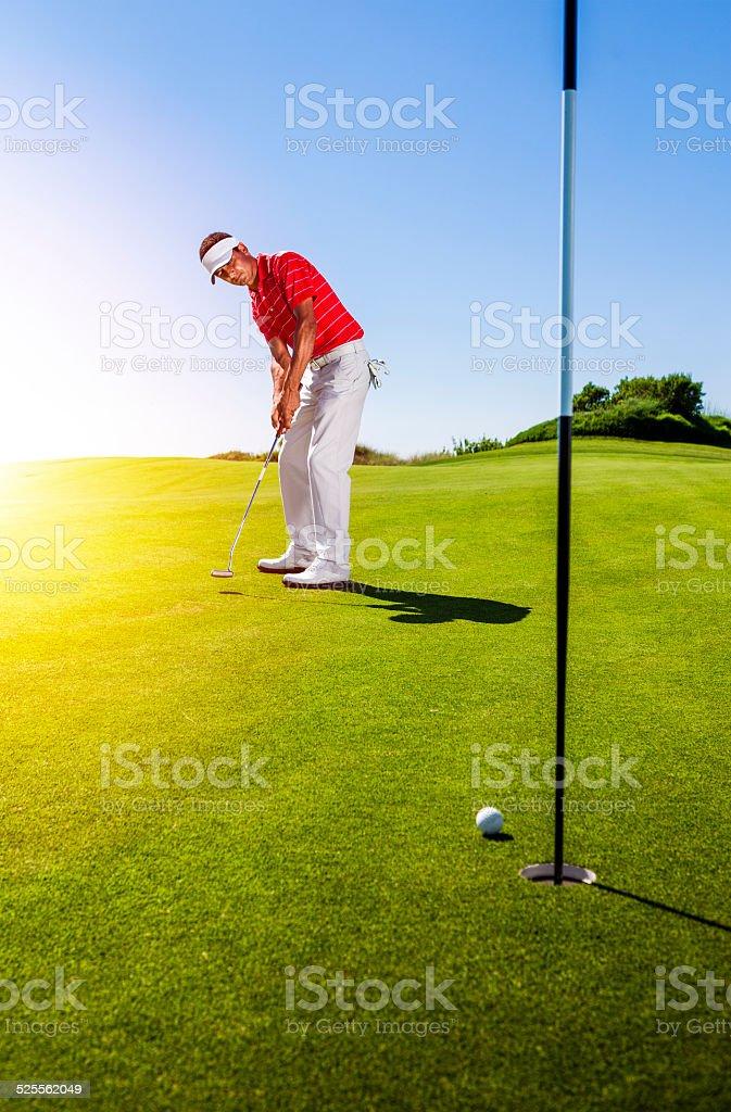 Golfer putting ball stock photo
