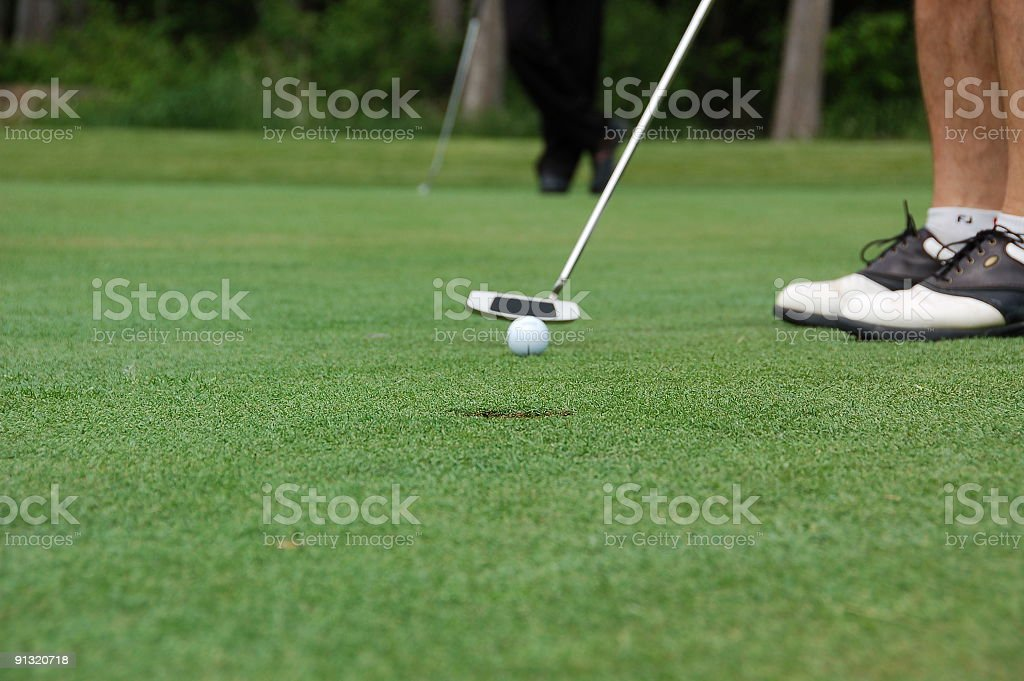 Golfer putting on the green.