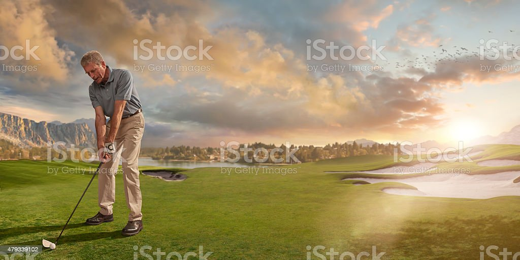 Golfer Ready to Play Shot on Course At Sunset stock photo