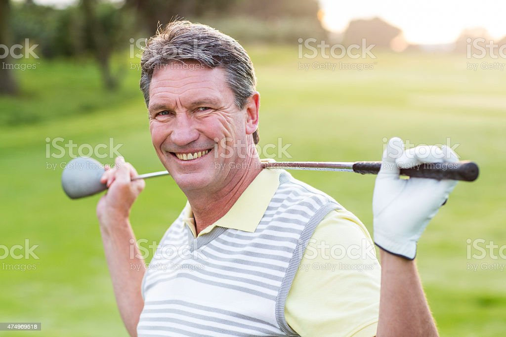 Golfer standing and swinging his club smiling at camera stock photo
