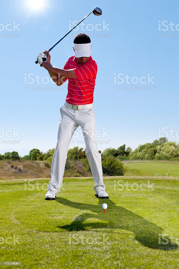 A golfer swinging a club on the course stock photo