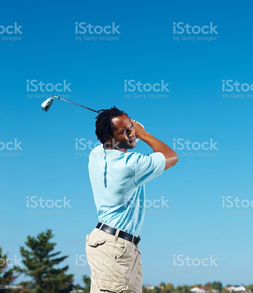 Golfer swinging a golf bat against sky royalty-free stock photo