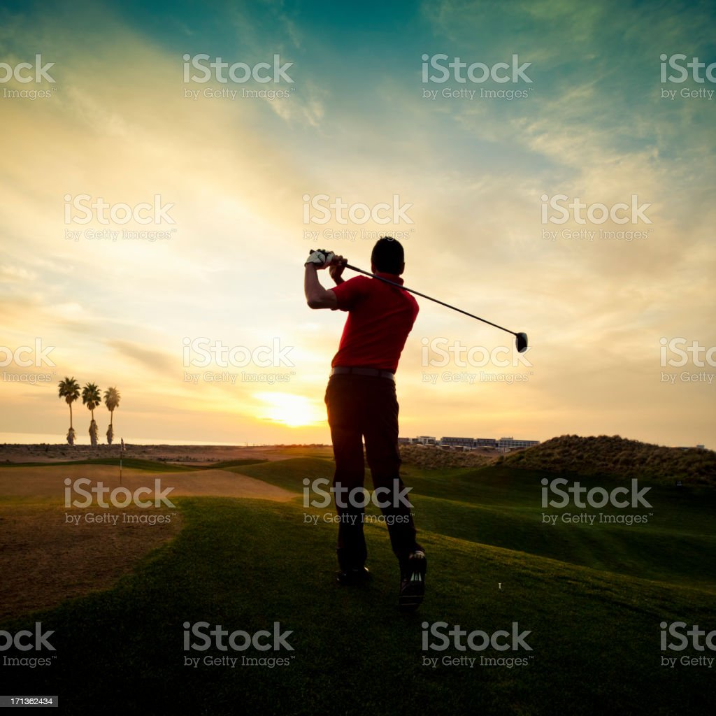 Golfer swinging at sunset stock photo