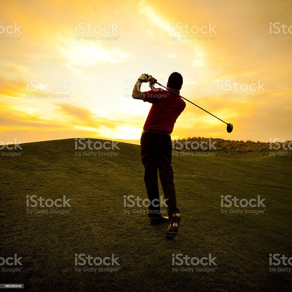 Golfer swinging at sunset stock photo