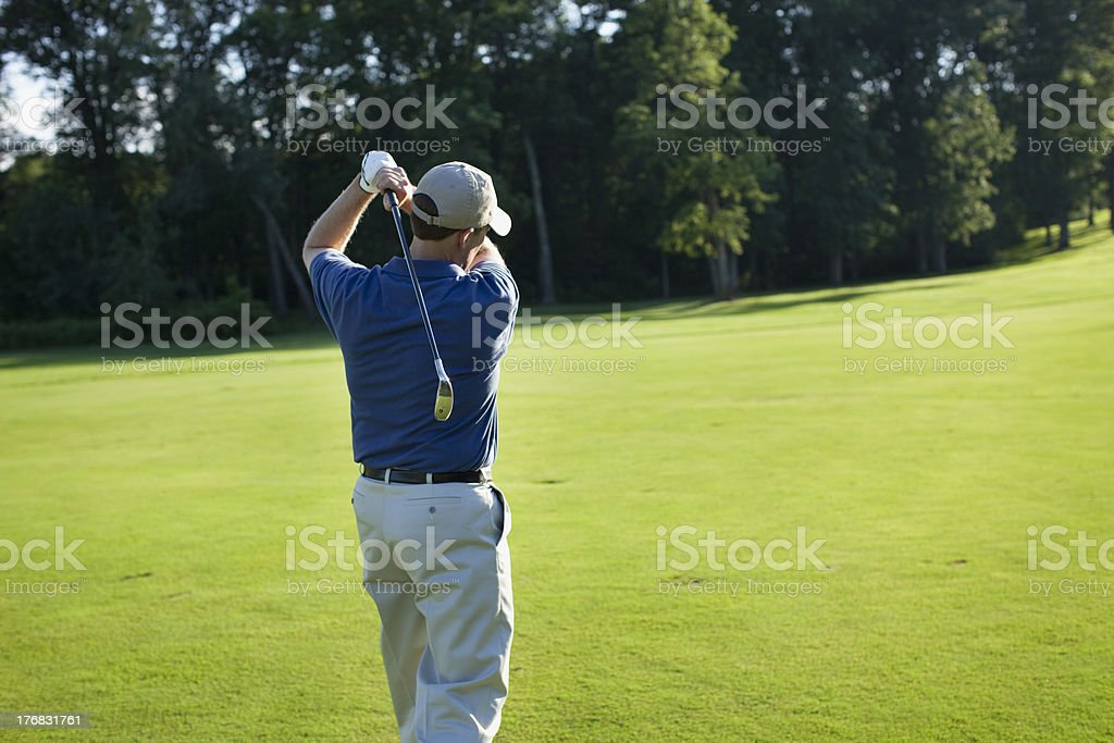 Golfer swinging club in late afternoon sunlight royalty-free stock photo