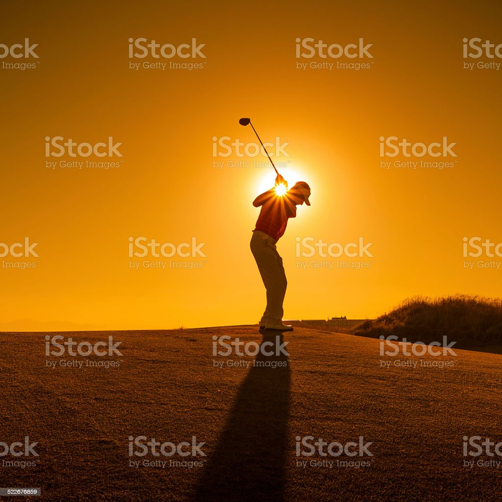 Golfer swinging stock photo