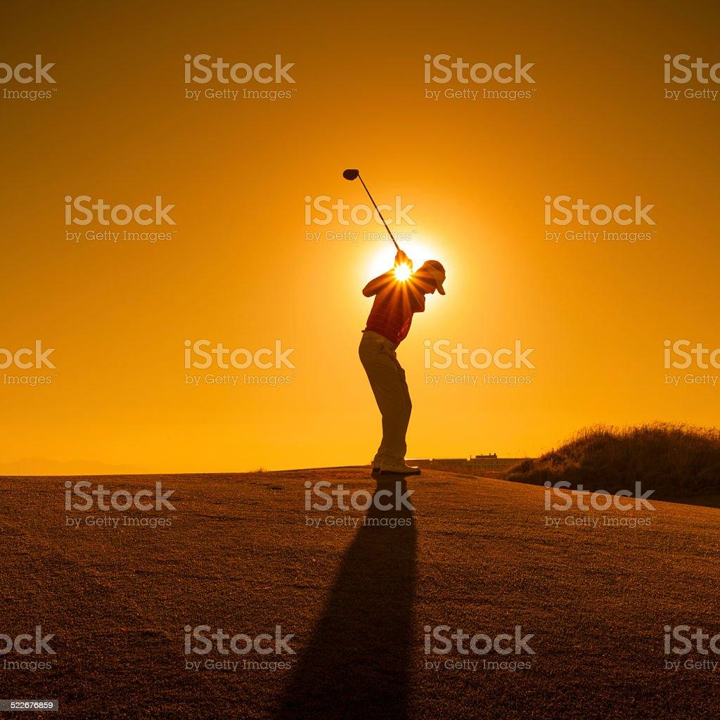 Golfer swinging stock photo