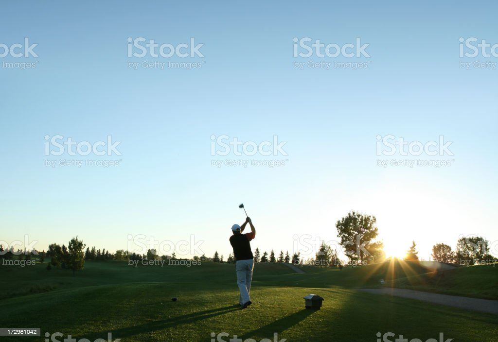 A golfer swings his driver in the early morning stock photo