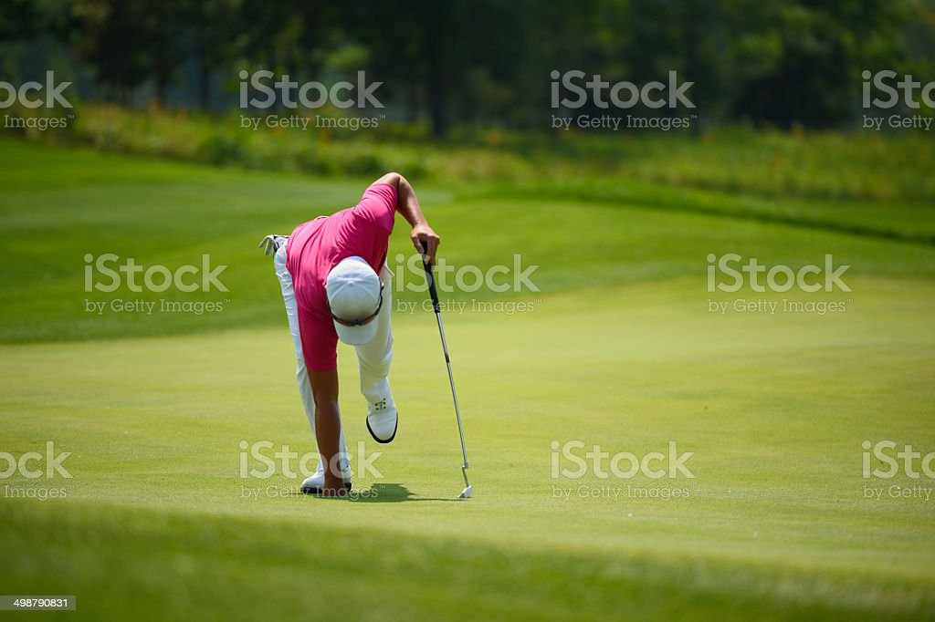 Golfer Taking Ball From Hole After Win stock photo