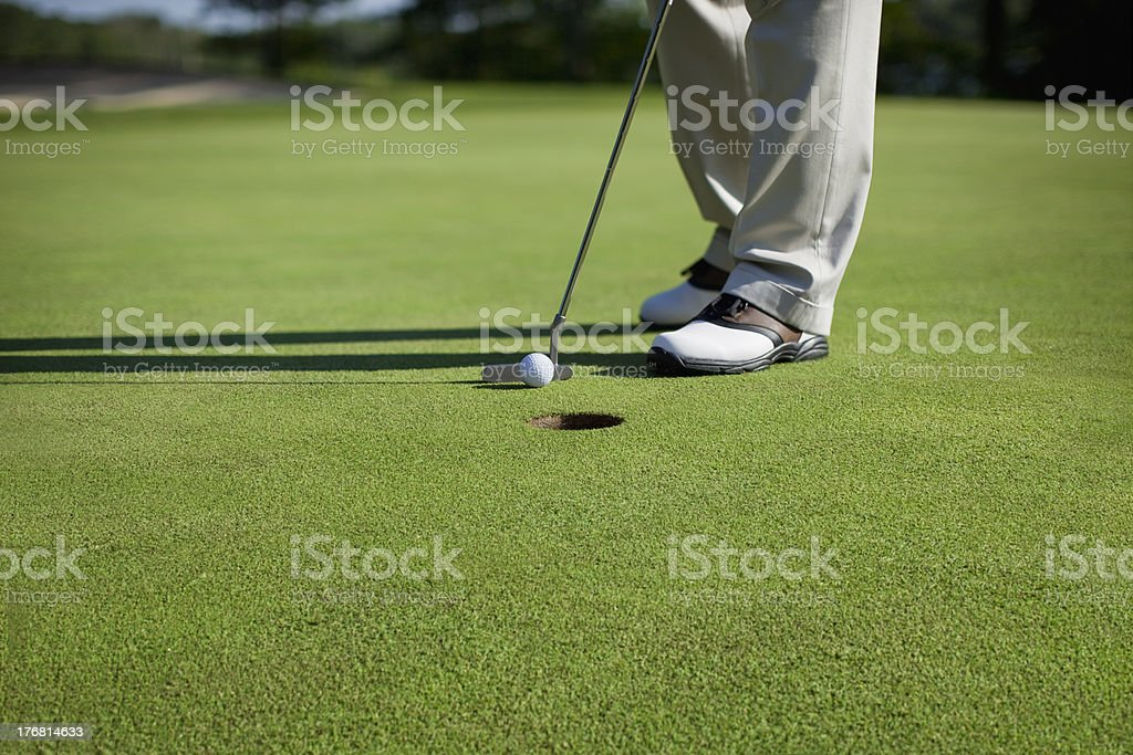 Golfer tapping in short putt stock photo