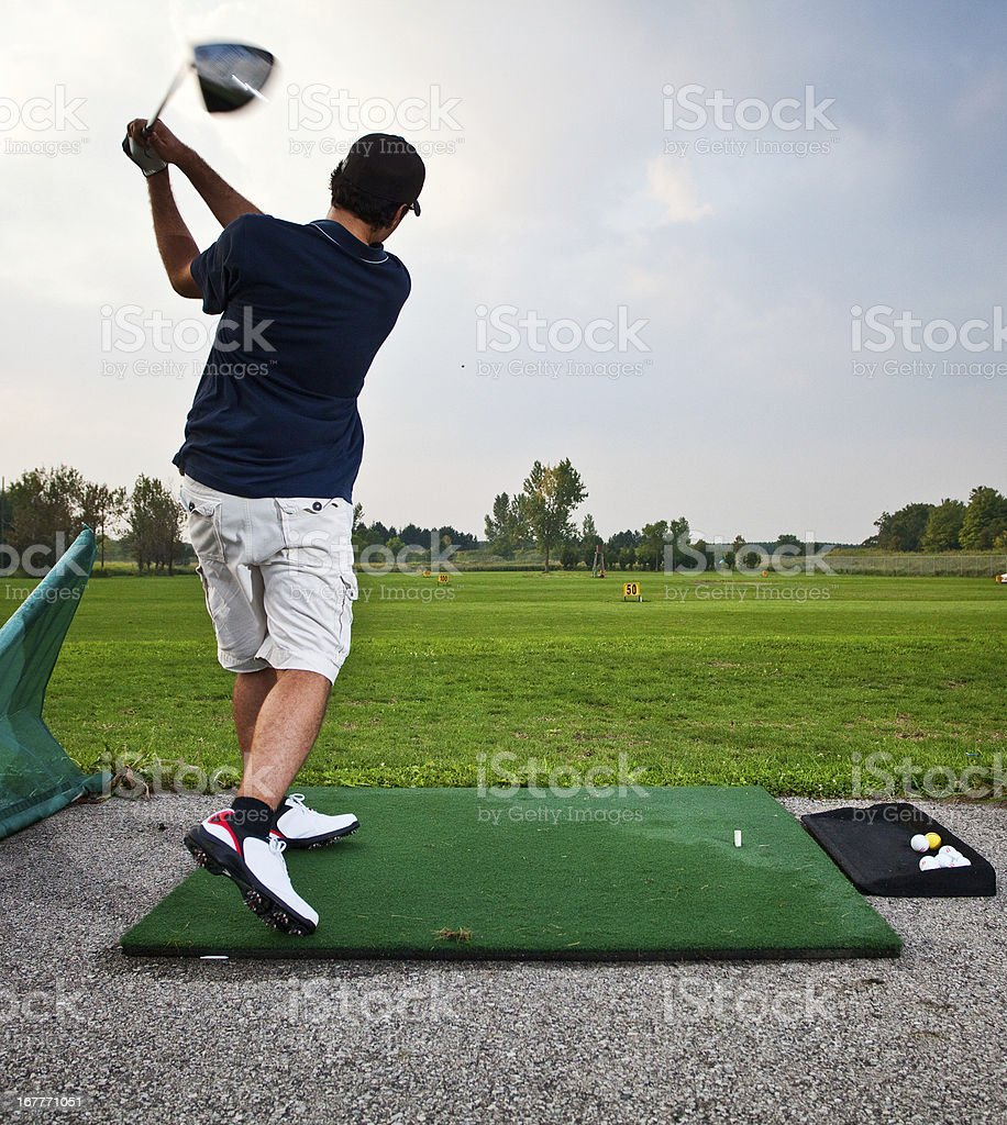 Golfer teeing off at a driving range stock photo