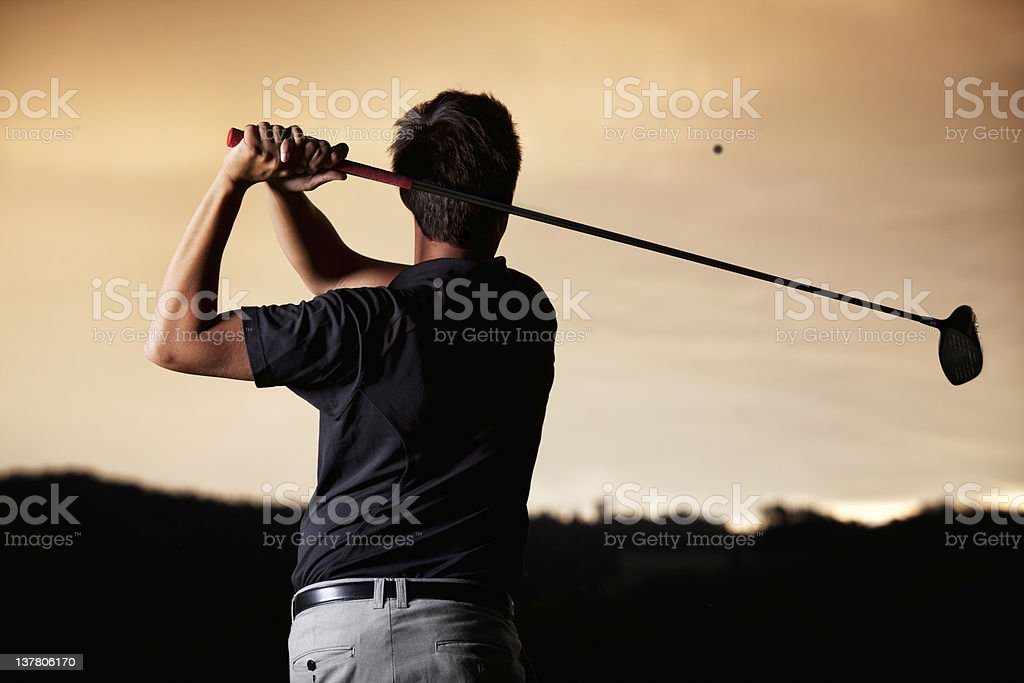 Golfer teeing off at sunset. stock photo