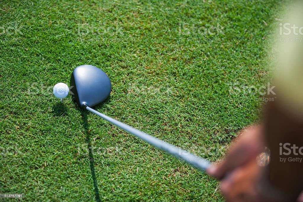 Golfer teeing off on golf course green stock photo