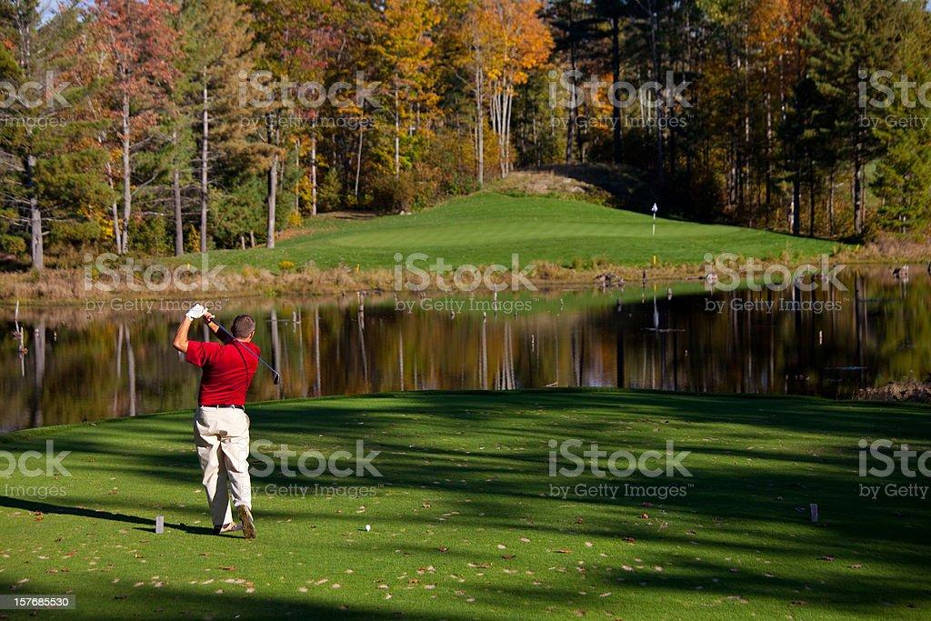 Golfer teeing off over the water hazard. stock photo