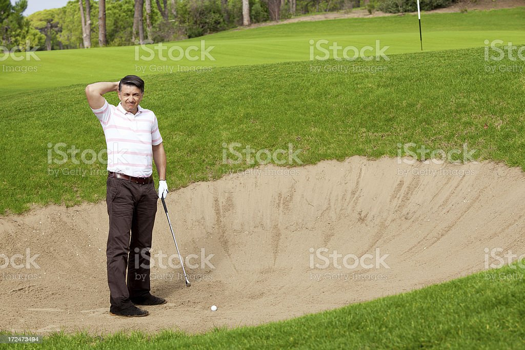 Golfer thinks how to get the ball out of trap stock photo