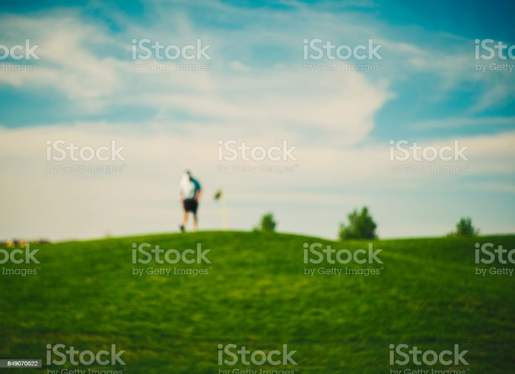Golfer walking across golf course with head down stock photo