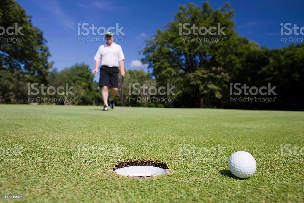 Golfer walks up to his golf ball by the hole. stock photo