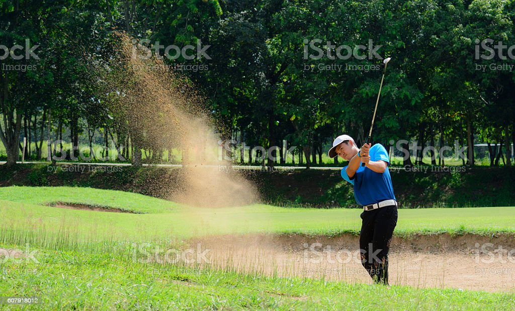 Golfers hit the ball in the sand. Speed and Strength stock photo